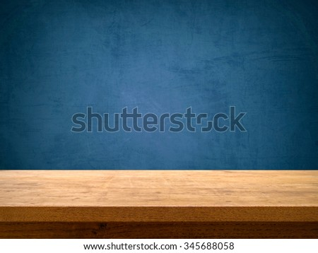 Empty wooden table on blue chalkboard background - stock photo