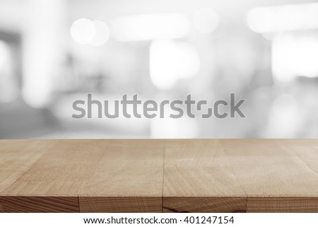 Empty wooden table on coffee shop blur background. - stock photo