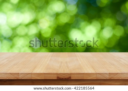 Empty wooden table on natural green background.