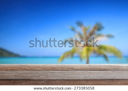 Empty wooden table on the beach, blurred filter effect. - stock photo