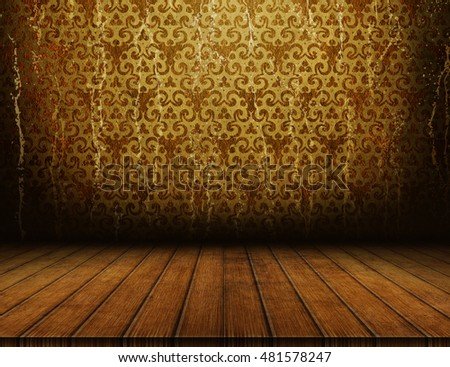 Empty wooden table over grunge gold ornamental wallpaper for product montage and presentation. Dark interior template.