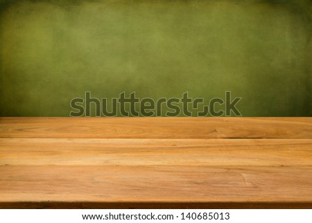 Empty wooden table over grunge green background. Perfect for product montage.