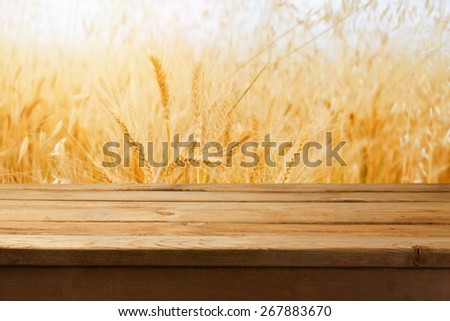 Empty wooden table over wheat field background - stock photo