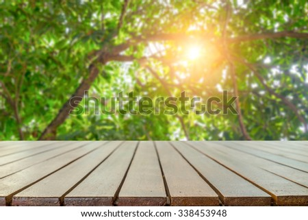 Empty wooden table platform over Nature bokeh garden background for presentation product.