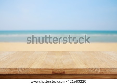 Empty wooden table top on the beach. - stock photo