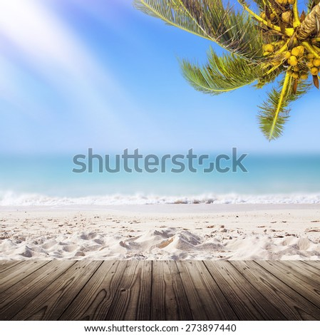 Empty wooden table. Tropical white sand beach background. Sunshine, coconut palm tree and ocean.  - stock photo