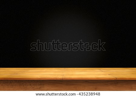 Empty wooden table with black wall background. For display or montage your products.