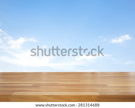Empty wooden table with blue sky and cloud, product display - stock photo