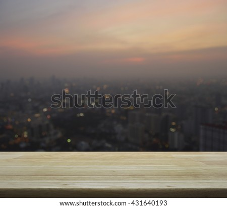 Empty wooden table with blurred aerial view of cityscape on warm light sundown, for your product display montage