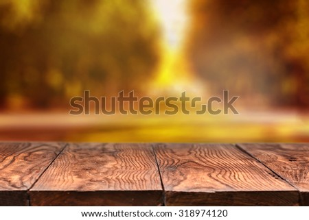 empty wooden table with blurred autumn natural background with bokeh - stock photo