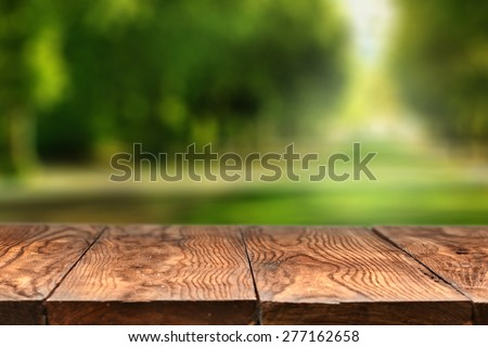 Empty wooden table with blurred city park on background, natural background with bokeh - stock photo