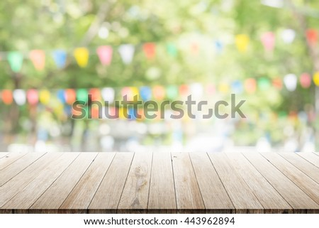 Empty wooden table with blurred party on background. fun / spring concept - stock photo