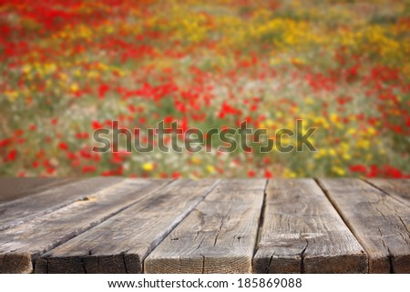Empty wooden table with field of flowers background. can be used for product display  - stock photo