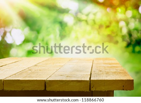 Empty wooden table with garden bokeh for a catering or food background with a country outdoor theme - stock photo
