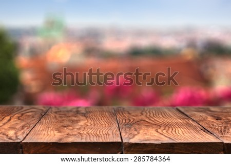 Empty wooden table with Prague on background with natural bokeh - stock photo