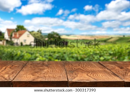 Empty wooden table with vineyard landscape in France on background - stock photo