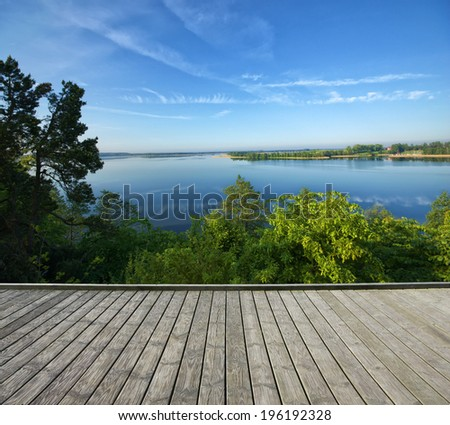 Empty wooden terrace with top view of beautiful lake in the background - stock photo