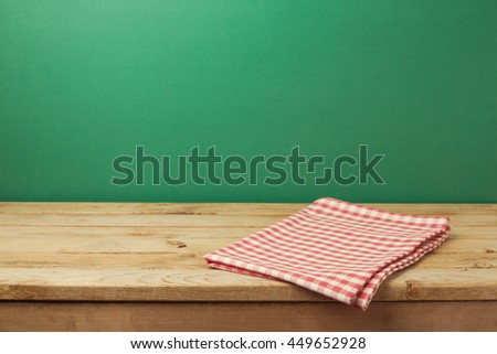 Empty wooden vintage table with red checked tablecloth over green wall background - stock photo