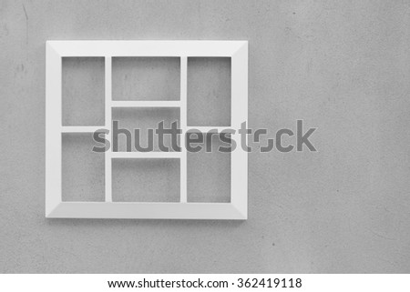 Empty wooden white picture frame on cement wall.
