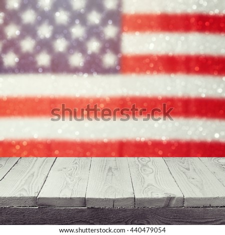 Empty wooden white table over USA flag bokeh background. USA national holidays background. 4th of July celebration. Ready for product display montage. - stock photo