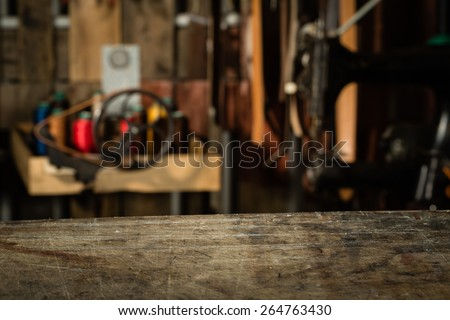Empty working desk with the scratches. Blurred background of leather workshop. Copy space. - stock photo