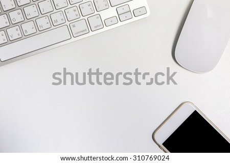 Empty workspace. View from above on the clean, well organized working space framed by keyboard, mouse and smart-phone - stock photo