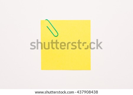 Empty yellow notepaper with green paper clip - stock photo