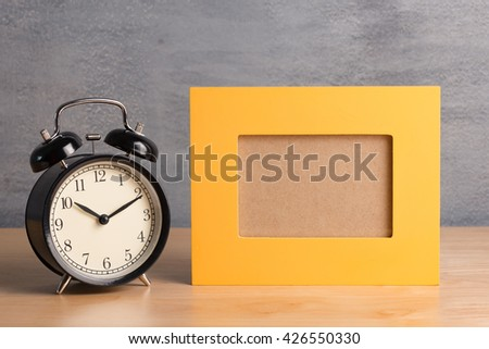 Empty yellow picture frame with black clock on wood table