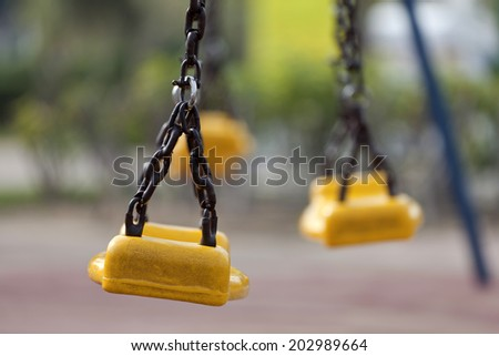 Empty yellow plastic swings on modern playground with selective focus - stock photo