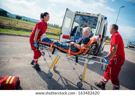 EMT team provide first aid on the street - Stock Image - stock photo