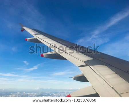 En route to London - January 2018: The wing of an airliner in flight against a background of blue sky