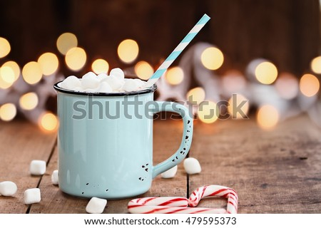 Enamel cup of hot cocoa with marshmallows and candy canes in the shape of a heart against rustic background with beautiful Christmas lights of bokeh. Could also be coffee. Perfect winter time treat.