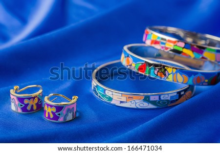 enamel earrings and bracelet on blue cloth - stock photo