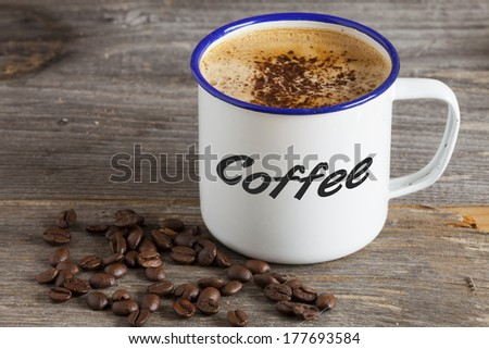 "Enamel Mugs with hot Coffee and Coffee Beans on a rustic wooden board with the Word ""Coffee"" on the Cup"