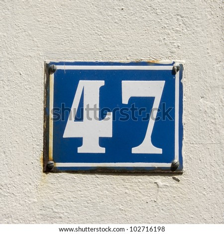 enameled house number forty seven. White lettering on a cobalt blue background - stock photo