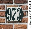 enameled house number nine hundred and seventy three. Dark green lettering on a white background - stock photo