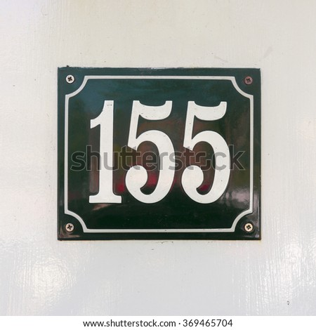 Enameled house number one hundred and fifty five. White numerals on a green background. - stock photo