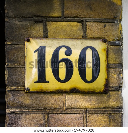 enameled house number one hundred and sixty . Black lettering on a yellowish plate. - stock photo