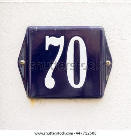 Enameled house number seventy - stock photo
