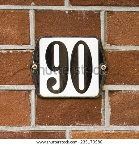 enameled house  number shield ninety, black numerals on a white background - stock photo