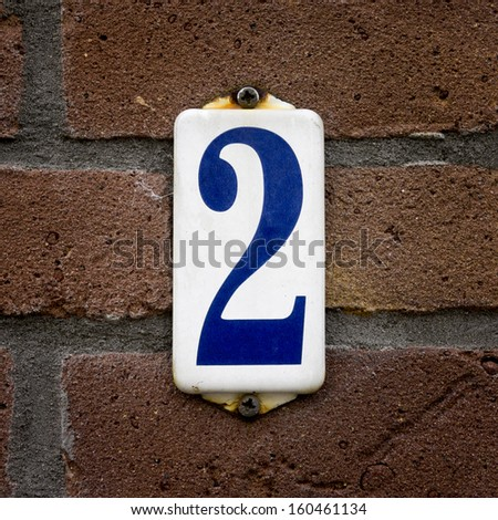 enameled house number two, Blue lettering on a white background - stock photo
