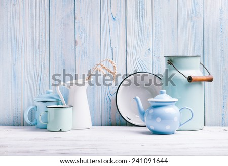 Enamelware on the kitchen table over blue wooden wall - stock photo