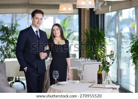 Enamored and romantic evening in the restaurant. Young couple visits a restaurant. woman holding a man's arm while the man and woman looking at the camera - stock photo