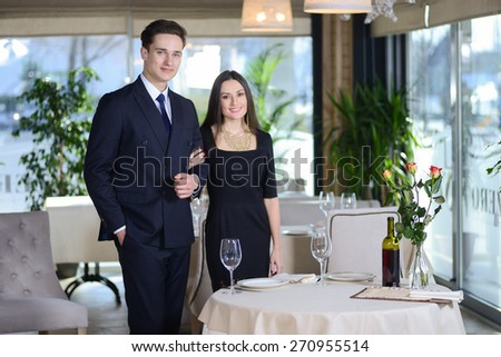 Enamored evening in the restaurant. Young couple visits a restaurant. woman holding a man's arm while the man and woman looking at the camera - stock photo