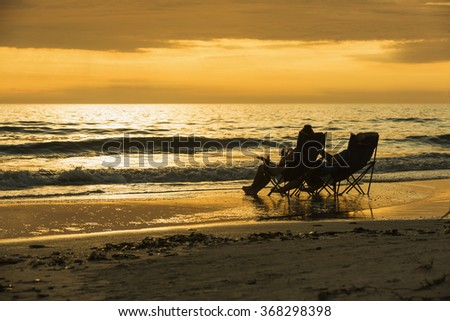 Enamored young couple sitting on chairs on the beach watching amazing colored sunset on the beach in Fort Myers Beach on the west coast of Florida. - stock photo