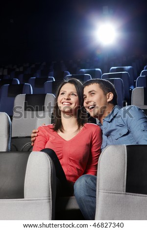 Enamoured laughing couple at a cinema on a forward background - stock photo