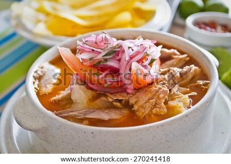 Encebollado, fish stew, served with banan chips and lemon. Typical ecuadorian dish, Ecuador. - stock photo