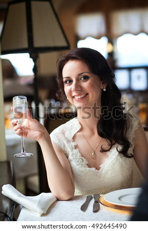 Enchanting bride holds glass with cold champagne while she sits at the table
