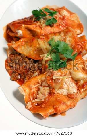 Enchiladas - meat-stuffed tortillas topped with spicy tomato salsa and cheese - on a plate. - stock photo