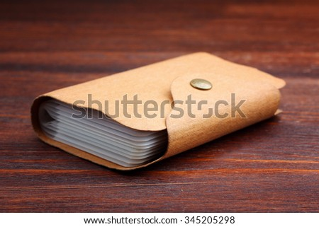 enclosed business card holder, back cover made of natural material, lying on brown wooden Desk.